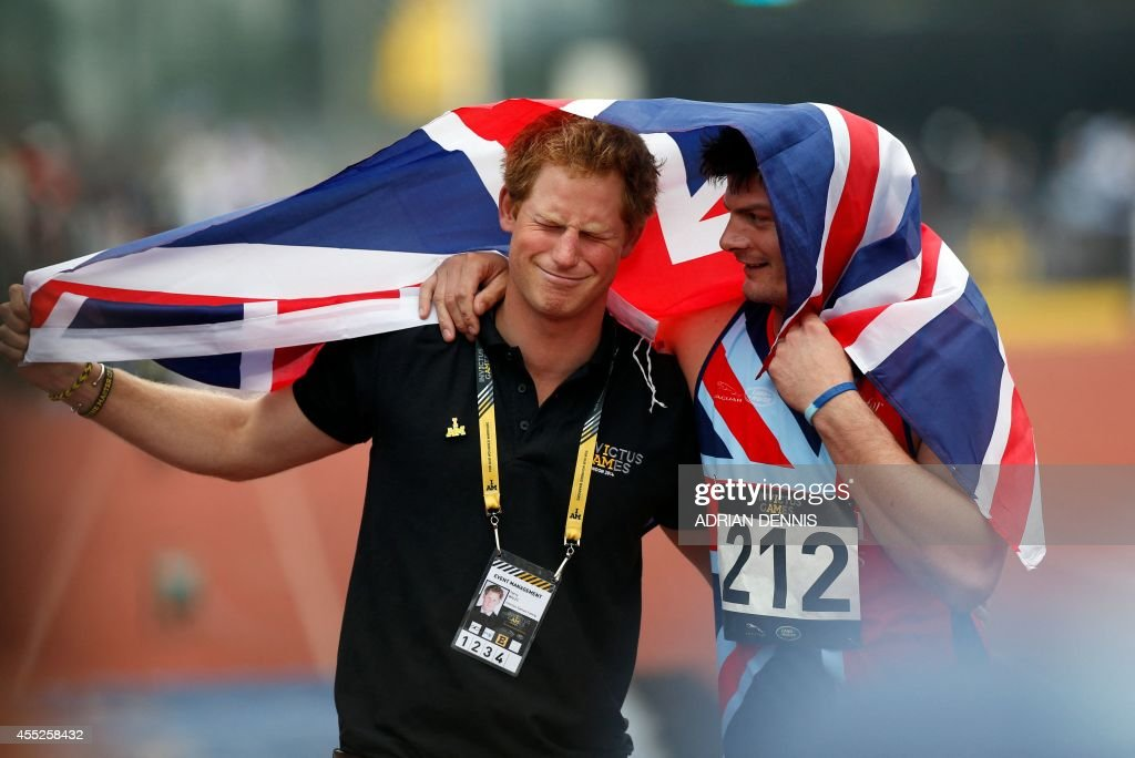 Britain's Prince Harry (L) celebrates with Great Britain's David Henson after the latter won the 200m men ambulant IT2 race during the athletics event of the Invictus Games at Queen Elizabeth II Park in London on September 11, 2014. More than 400 wounded troops from 13 countries -- both serving and veter -- will go for gold across nine sports at Prince Harry's Invictus Games in London Between 10-14 September.