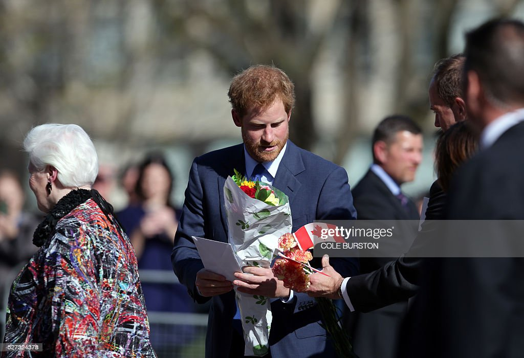 Britain's Prince Harry collects his gifts as he greets admirers outside of Queens Park in Toronto, Canada on May 2, 2016 after spending the day in the city promoting the 2017 Invictus Games, which will be held in Toronto. / AFP / Cole Burston