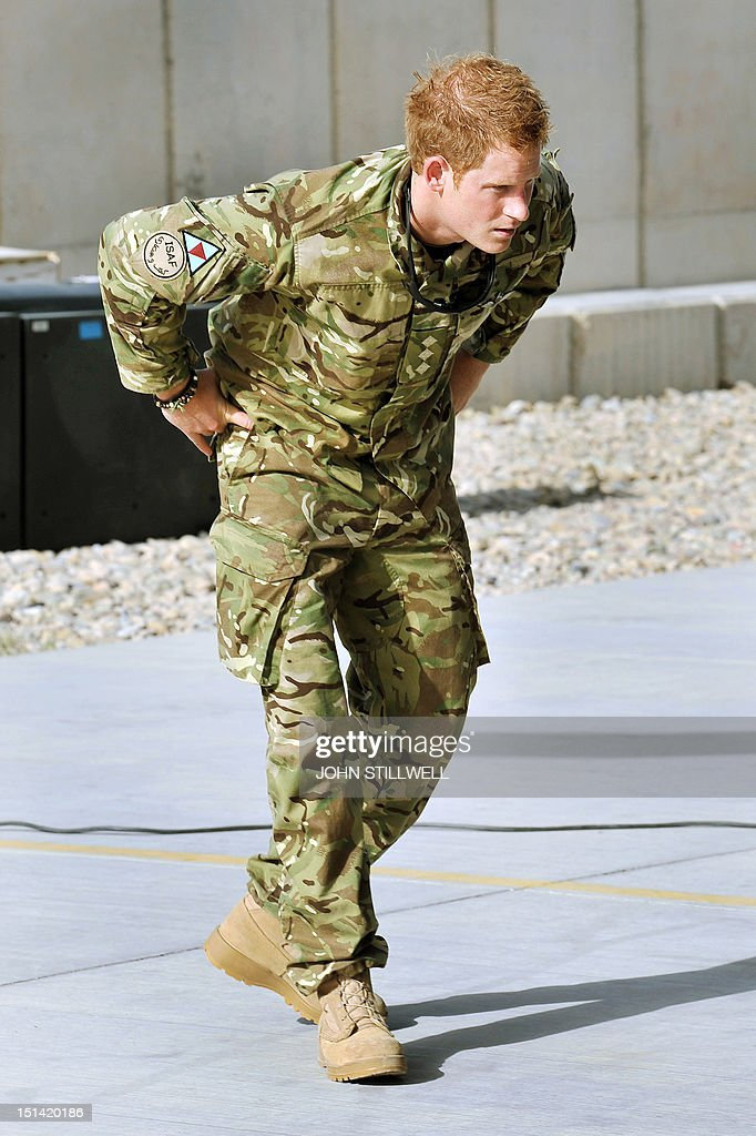 Britain's Prince Harry examines the 30mm cannon of an Apache helicopter upon his arrival at Camp Bastion in Afghanistan, on September 7, 2012. Britain's Prince Harry is back in Afghanistan to serve as a military helicopter pilot four years after his previous deployment there had to be cut short, the Ministry of Defence said on Friday. AFP PHOTO/JOHN STILLWELL/POOL