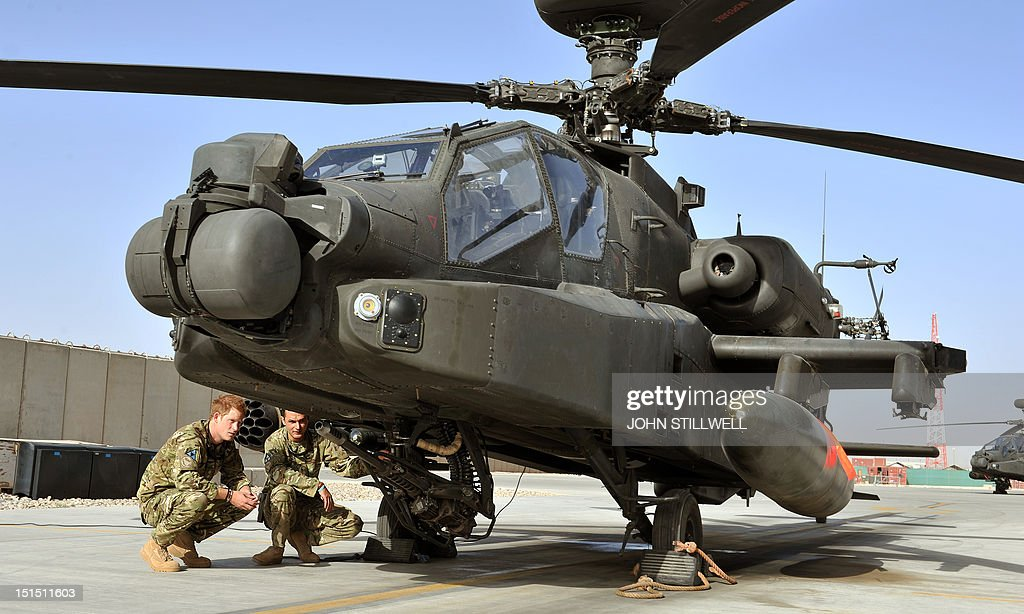 Britain's Prince Harry examines the 30mm cannon of an Apache helicopter with a member of his 622 Squadron, 3 Regiment Army Air Corps, part of 16 Air Assault Brigade, at Camp Bastion in Helmand Province, Afghanistan on September 7, 2012, where he will be operating from during his tour of duty as a co-pilot gunner. Prince Harry is back in Afghanistan to serve as a military helicopter pilot four years after his previous deployment there had to be cut short, the Ministry of Defence said.