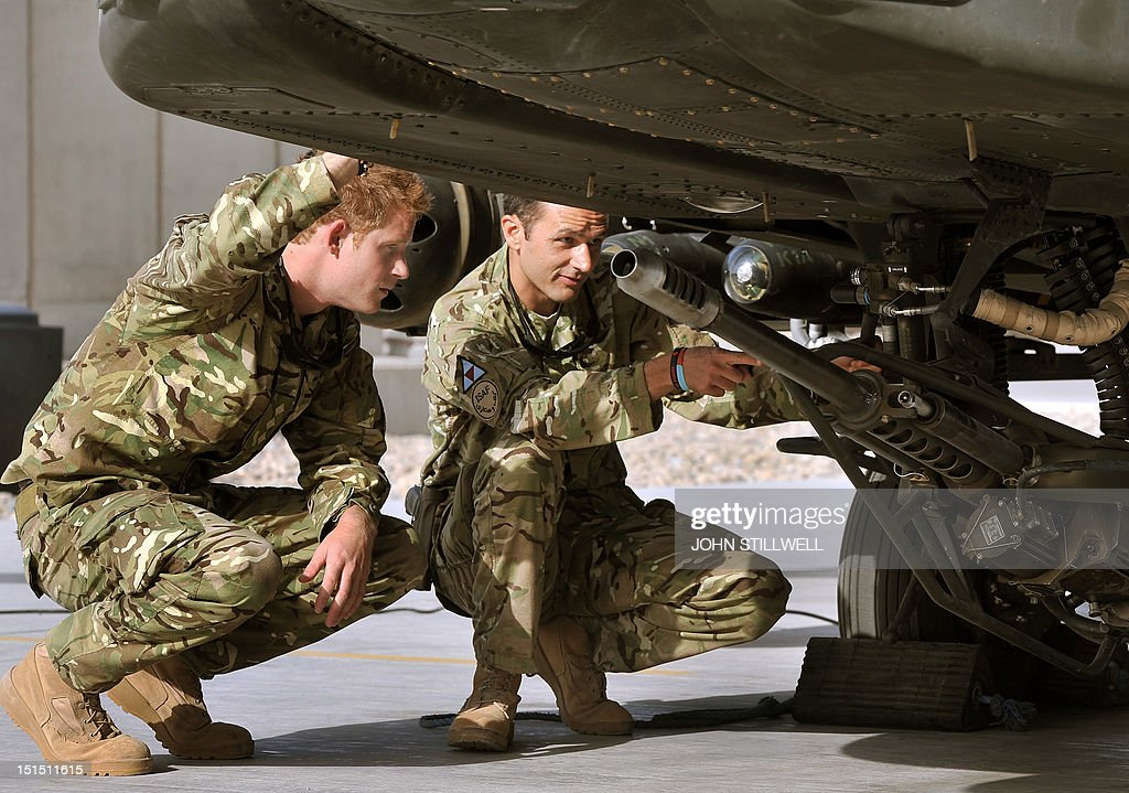 Britain's Prince Harry examines the 30mm cannon of an Apache helicopter with a member of his 622 Squadron, 3 Regiment Army Air Corps, part of 16 Air Assault Brigade, at Camp Bastion in Helmand Province, Afghanistan on September 7, 2012, where he will be operating from during his tour of duty as a co-pilot gunner. Prince Harry is back in Afghanistan to serve as a military helicopter pilot four years after his previous deployment there had to be cut short, the Ministry of Defence said. AFP PHOTO / POOL / JOHN STILLWELL