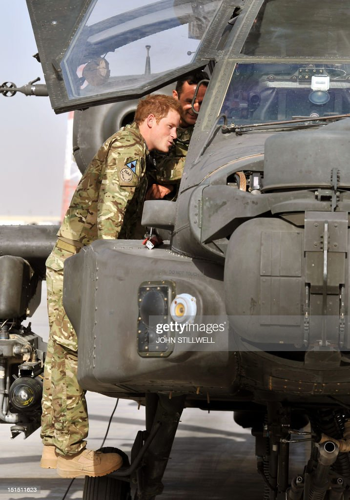 Britain's Prince Harry examines the interior of an Apache helicopter with a member of his 622 Squadron, 3 Regiment Army Air Corps, part of 16 Air Assault Brigade, at Camp Bastion in Helmand Province, Afghanistan on September 7, 2012, where he will be operating from during his tour of duty as a co-pilot gunner. Prince Harry is back in Afghanistan to serve as a military helicopter pilot four years after his previous deployment there had to be cut short, the Ministry of Defence said. AFP PHOTO / POOL / JOHN STILLWELL