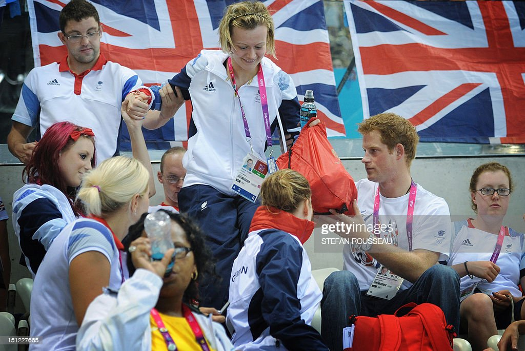 Britain's Prince Harry (R) helps Britain's swimmer Hannah Russell to her seat at the Aquatics Centre during the London 2012 Paralympic Games at the Olympic Park on September 4, 2012.