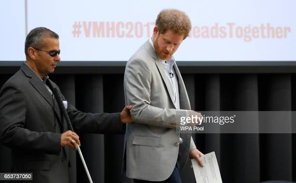 Britain's Prince Harry helps former member of the US Armed Forces Ivan Castro as they arrive on stage at King's College on March 16 2017 in London...