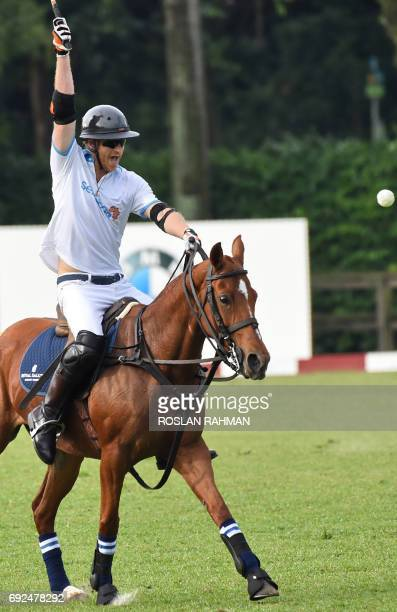 Britain's Prince Harry hits the polo ball with his mallet as he takes part in the Sentebale Royal Salute Polo Cup in Singapore on June 5 2017 Prince...