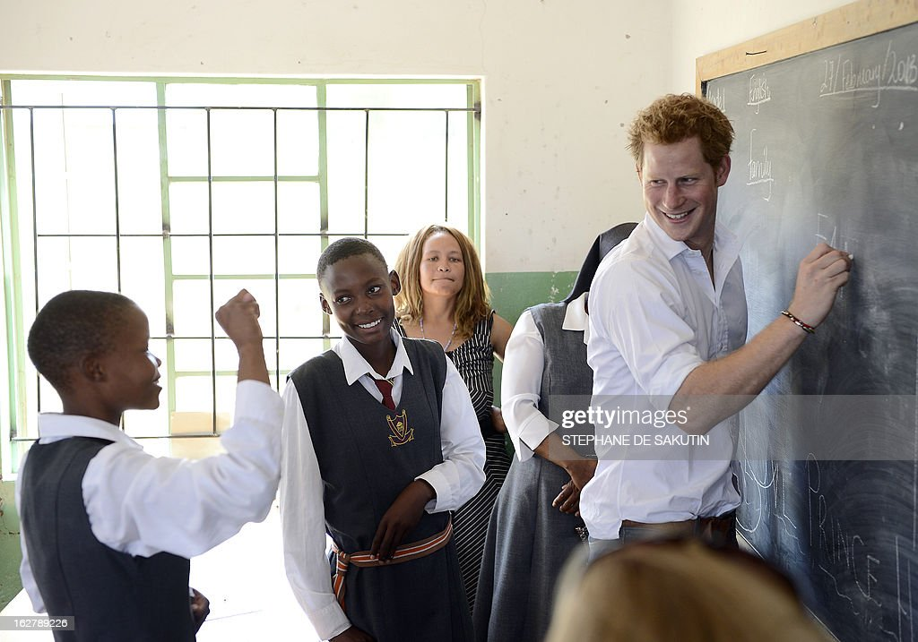 Britain's Prince Harry (R) interacts with a deaf girl on February 27, 2013 at the Kananelo Center for the Deaf in Maseru. The prince visited his charity projects in Lesotho on February 27, finding time to perform traditional dance moves with children during his return visit to the southern African kingdom. AFP PHOTO / STEPHANE DE SAKUTIN