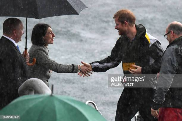 Britain's Prince Harry is greeted by New South Wales' Premier Gladys Berejiklian as he arrives in torrential rain on a police rib at Sydney's...
