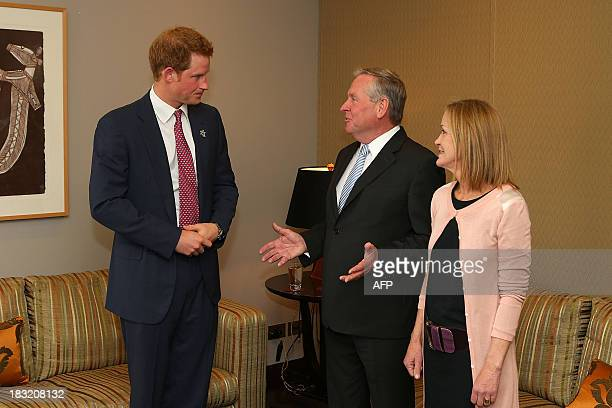 Britain's Prince Harry is greeted by West Australian Premier Colin Barnett and his wife Lyn Burnett after arriving in Perth on October 6 2013 Prince...