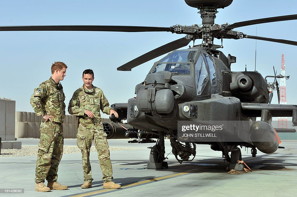 Britain's Prince Harry (L) is shown the Apache flight-line by a member of his squadron (name not provided) at Camp Bastion in Helmand Province, Afghanistan on September 7, 2012, where he will be operating from during his tour of duty as a co-pilot gunner. Prince Harry is back in Afghanistan to serve as a military helicopter pilot four years after his previous deployment there had to be cut short, the Ministry of Defence said on September 7.