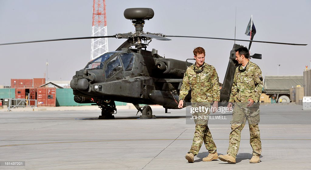 Britain's Prince Harry (L) is shown the Apache helicopter flight-line by a member of his 622 Squadron, 3 Regiment Army Air Corps, part of 16 Air Assault Brigade, at Camp Bastion in Helmand Province, Afghanistan on September 7, 2012, where he will be operating from during his tour of duty as a co-pilot gunner. Prince Harry is back in Afghanistan to serve as a military helicopter pilot four years after his previous deployment there had to be cut short, the Ministry of Defence said on September 7.
