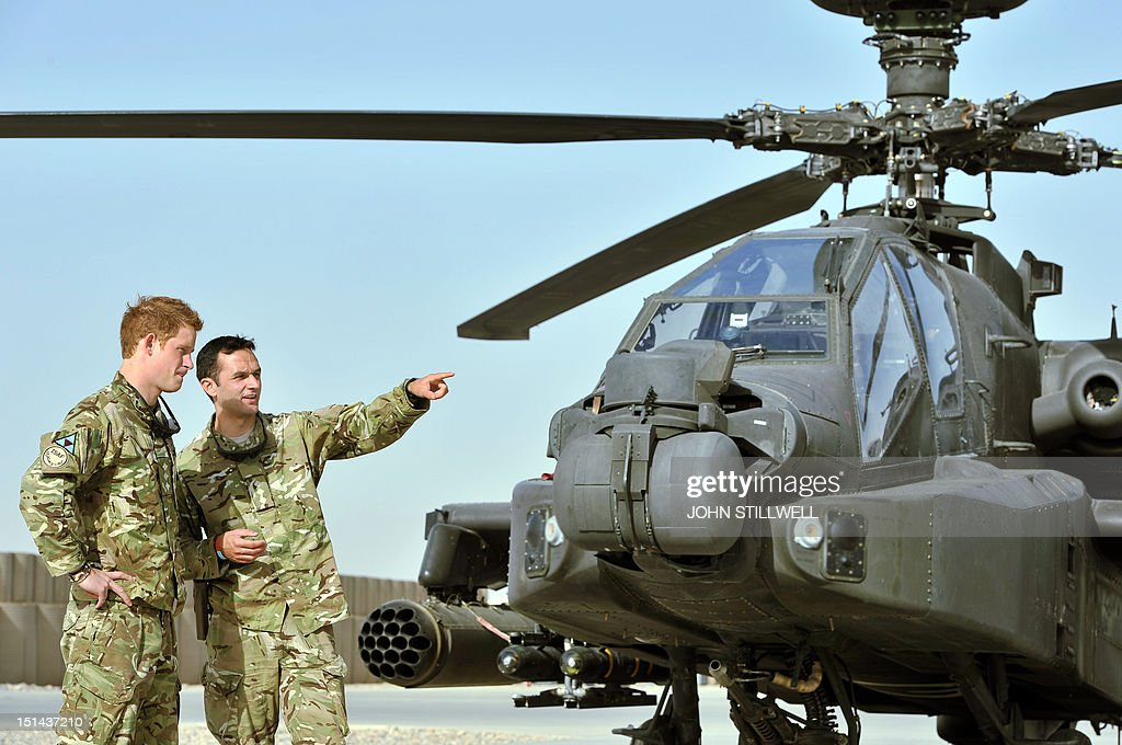 Britain's Prince Harry (L) is shown the Apache helicopter flight-line by a member of his 622 Squadron, 3 Regiment Army Air Corps, part of 16 Air Assault Brigade, at Camp Bastion in Helmand Province, Afghanistan on September 7, 2012, where he will be operating from during his tour of duty as a co-pilot gunner. Prince Harry is back in Afghanistan to serve as a military helicopter pilot four years after his previous deployment there had to be cut short, the Ministry of Defence said on September 7. AFP PHOTO / POOL / JOHN STILLWELL