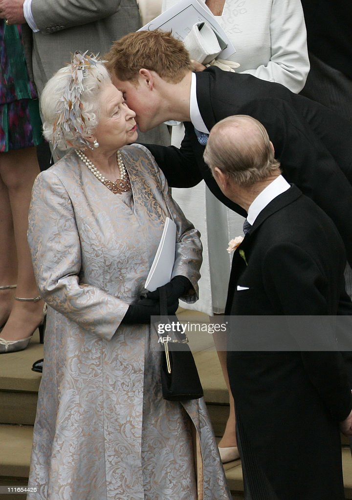 Britain's Prince Harry kisses his grandmother Queen Elizabeth II, as Prince Philip, Duke of Edinburgh, (R), looks on, as they leave St George's Chapel in Windsor, England, after attending Peter Phillips, Queen Elizabeth II's grandson, and Canadian Autumn Kelly's marriage ceremony, on May 17, 2008. AFP PHOTO Sang Tan/ Pool