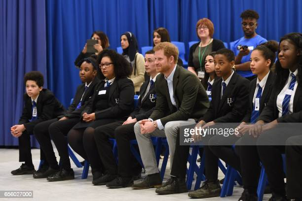Britain's Prince Harry listens to a performance by pupils from the Yes You Can personal development project which works to help underperforming Year...
