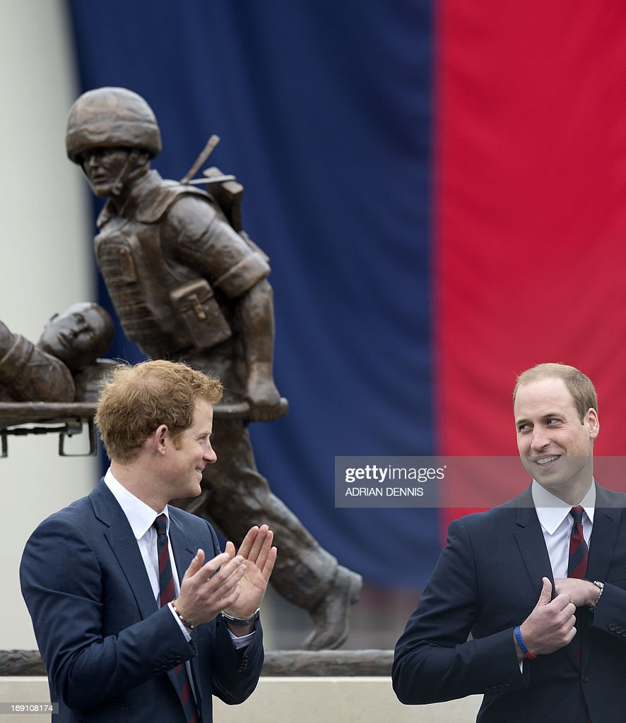 Britain's Prince Harry (L) looks at his brother Prince William, Duke of Cambridge (R), during a visit to Tedworth House, a recovery centre run by the Help for Heroes charity that offers care and support to injured service personnel, in Tidworth, Wiltshire, southern England, on May 20, 2013. The Duke of Cambridge and Prince Harry will officially open four new Help for Heroes recovery centres, which form part of the Defence Recovery Capability. Prince William and Harry met wounded service personnel, veterans and their families to learn about the challenges they face. Help for Heroes is building, equipping and running four recovery centres to provide ongoing support for wounded, injured and sick service personnel and veterans. Tedworth House is the first centre to open, and has the capacity to accommodate 50 residents, 4 families and over 150 day visitors.