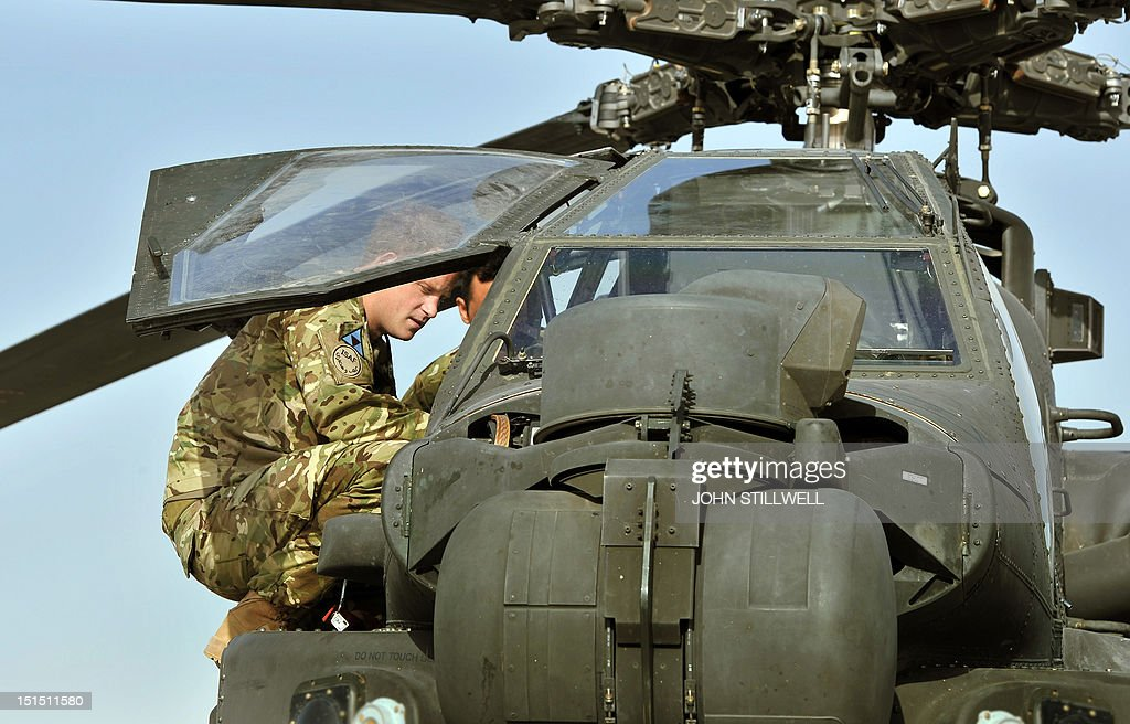 Britain's Prince Harry looks in the interior of an Apache helicopter with a member of his 622 Squadron, 3 Regiment Army Air Corps, part of 16 Air Assault Brigade, at Camp Bastion in Helmand Province, Afghanistan on September 7, 2012, where he will be operating from during his tour of duty as a co-pilot gunner. Prince Harry is back in Afghanistan to serve as a military helicopter pilot four years after his previous deployment there had to be cut short, the Ministry of Defence said.