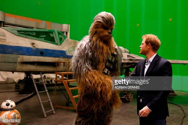 Britain's Prince Harry meets Chewbacca during a visit to the Star Wars film set at Pinewood Studios near Iver Heath west of London April 19 2016...