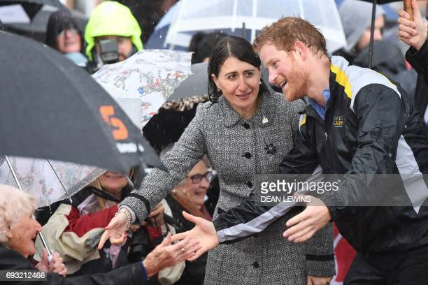 Britain's Prince Harry meets Daphne Dunne as New South Wales' Premier Gladys Berejiklian gestures during a walk around The Rocks in Sydney on June 7...