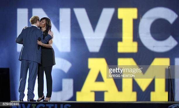 Britain's Prince Harry Patron of the Invictus Games Foundation greets US First Lady Michelle Obama on stage during opening ceremonies for the 2016...