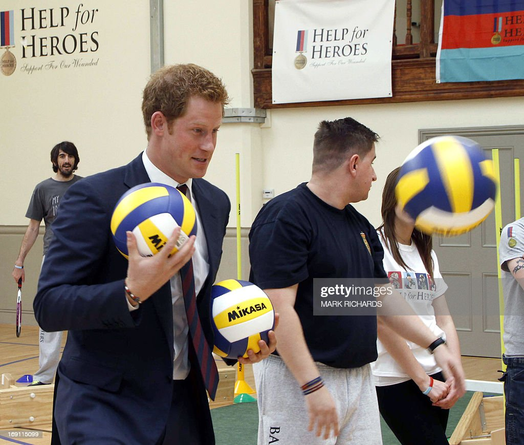 Britain's Prince Harry plays with balls during a visit to Tedworth House, a recovery centre run by the Help for Heroes charity that offers care and support to injured service personnel, in Tidworth, Wiltshire, southern England, on May 20, 2013. The Duke of Cambridge and Prince Harry will officially open four new Help for Heroes recovery centres, which form part of the Defence Recovery Capability.