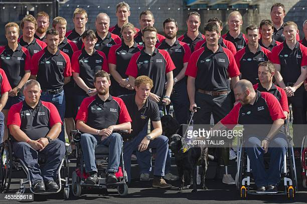 Britain's Prince Harry poses with injured service personnel during the announcement of the British team for the Invictus Games in London on August 13...