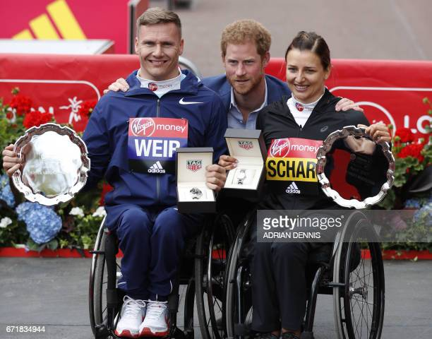 Britain's Prince Harry poses with wheelchair winners Britain's David Weir and Switzerland's Manuela Schar after the London marathon on April 23 2017...