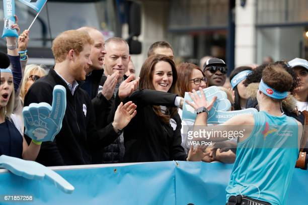 Britain's Prince Harry Prince William Duke of Cambridge and Catherine Duchess of Cambridge cheer on runners at a Heads Together cheering point along...
