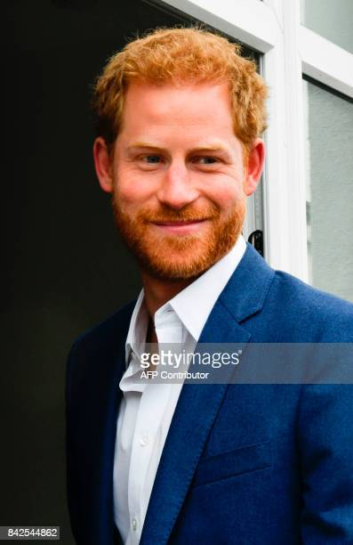 Britain's Prince Harry reacts as during his tour of Walking With The Wounded 's training house and facilities in Canada Street Manchester northwest...