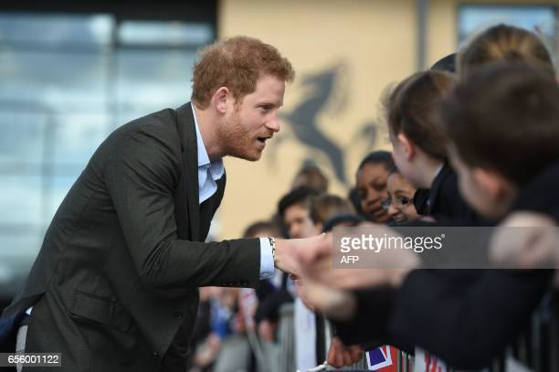 Britain's Prince Harry shakes hands with children as he leaves after meeting representatives of the Yes You Can personal development project which...