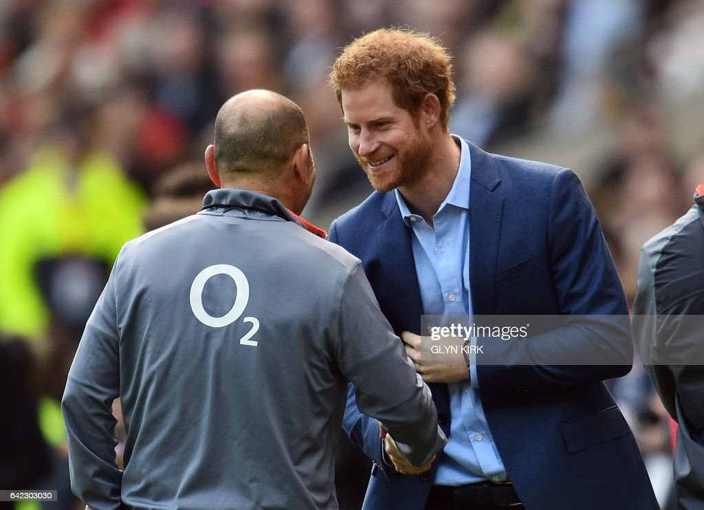 Britain's Prince Harry (R) shakes hands with England's Australian head coach Eddie Jones during a team training session at Twickenham Stadium in southwest London on February 17, 2017. / AFP / GLYN