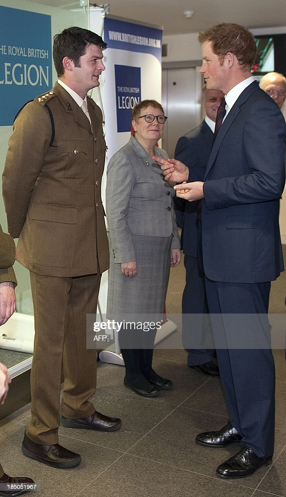 Britain's Prince Harry (R) speaks to British Army Captain Dave Henson during his visit to Imperial College in London on October 17, 2013 during which he officially opened the Royal British Legion Centre for Blast Injury Studies.