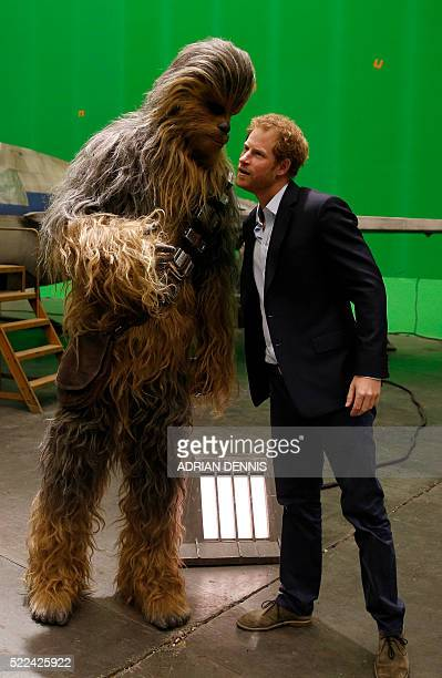 Britain's Prince Harry speaks with Chewbacca during a tour of the Star Wars sets at Pinewood studios in Iver Heath west of London on April 19 2016...