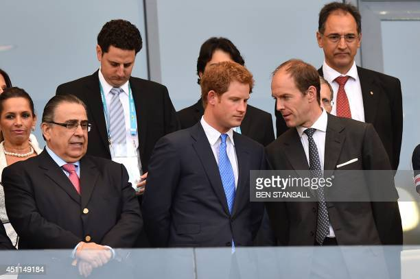 Britain's Prince Harry speaks with officials as he attends the Group D football match between Costa Rica and England at The Mineirao Stadium in Belo...