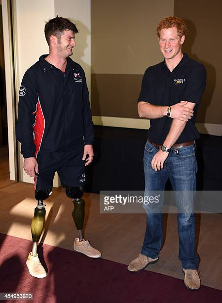 Britain's Prince Harry speaks with team GB's Dave Henson as he meets with team captains taking part in the upcoming Invictus Games in London on...