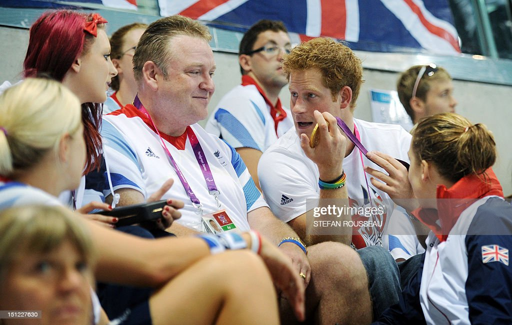 Britain's Prince Harry (R) talks with Britain's swimming gold medalist Jessica-Jane Applegate (L) as he holds her gold medal at the Aquatics Centre during the London 2012 Paralympic Games at the Olympic Park in London on September 4, 2012. AFP PHOTO / POOL / STEFAN ROUSSEAU