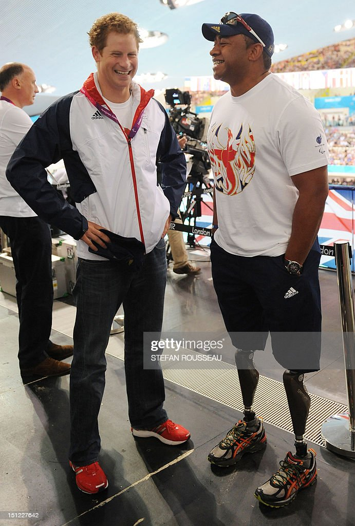 Britain's Prince Harry (L) talks with former British soldier and Paralympic athlete Derek Derenalagi at the Aquatics Centre during the London 2012 Paralympic Games at the Olympic Park in London on September 4, 2012.