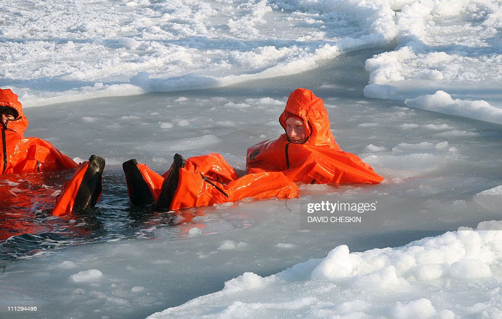 Britain's Prince Harry (R) tries out an immersion suit as he joins the Walking with the Wounded team for training on the island of Spitsbergen, situated between the Norwegian mainland and the North Pole, on March 30, 2011 for their last days of packing before setting off to walk to the North Pole. The team's expedition will last four weeks and see them cover up to 200 miles (320 kilometres) of the frozen Arctic Ocean on foot, pulling their own equipment in temperatures as low as minus 60 degrees Centigrade. AFP PHOTO/David Cheskin/WPA