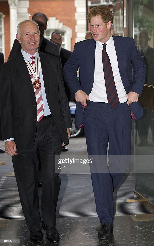 Britain's Prince Harry (R) walks alongside Vice Lord Lieutenant Wing Commander Dudgeon during his visit to Imperial College in London on October 17, 2013 during which he officially opened the Royal British Legion Centre for Blast Injury Studies.