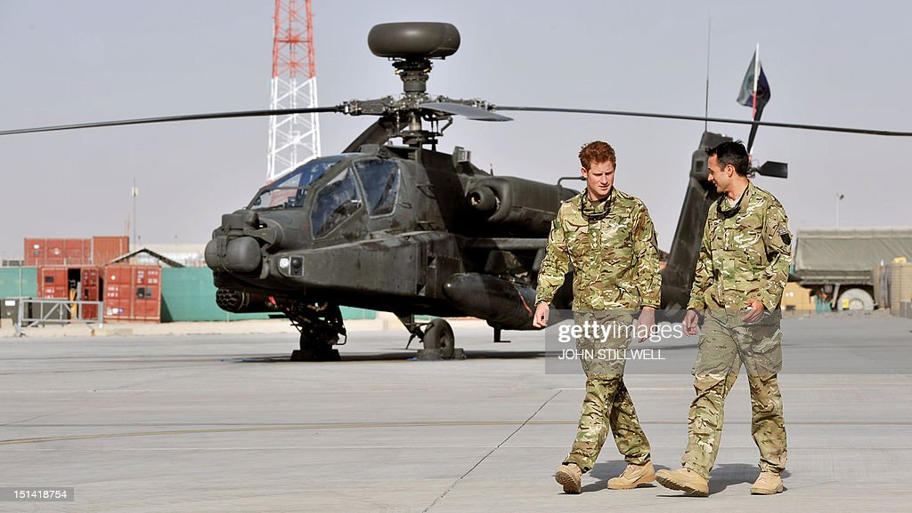 Britain's Prince Harry (2nd R) walks past an Apache helicopter upon his arrival at Camp Bastion in Afghanistan, on September 7, 2012. Britain's Prince Harry is back in Afghanistan to serve as a military helicopter pilot four years after his previous deployment there had to be cut short, the Ministry of Defence said on Friday.