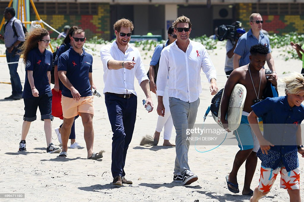 Britain's Prince Harry(C)walks with surfers and officials during a visit to development kids from the Surfers not Streetchildren organisation on Addington Beach in Durban on December 1, 2015. / AFP / ANESH