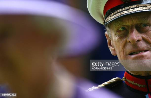 Britain's Prince Philip listens to a speech while standing behind his wife Queen Elizabeth II following a remembrance service commemorating 25 years...