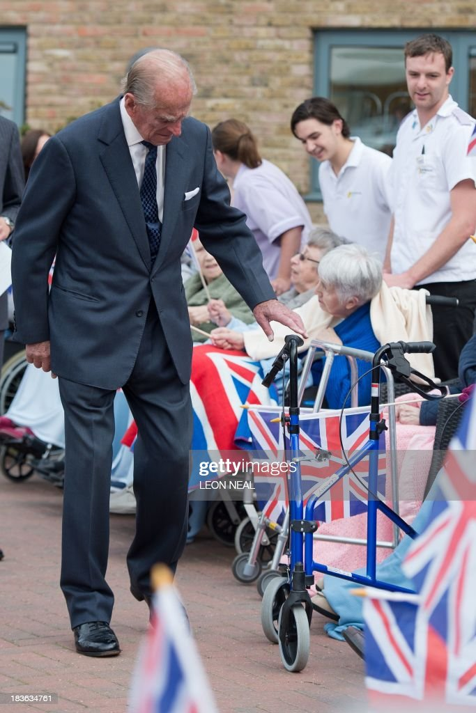 Britain's Prince Philip examines a rollator walking frame while meeting residents of the St Michael's Care Complex in Aylsham, eastern England, during an official visit on October 8, 2013.