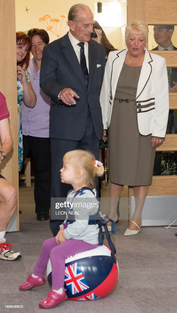 Britain's Prince Philip gestures as he watches residents exercise in the Green Lane View assisted-living residential home during an official visit to the St Michael's Care Complex in Aylsham, eastern England, on October 8, 2013.