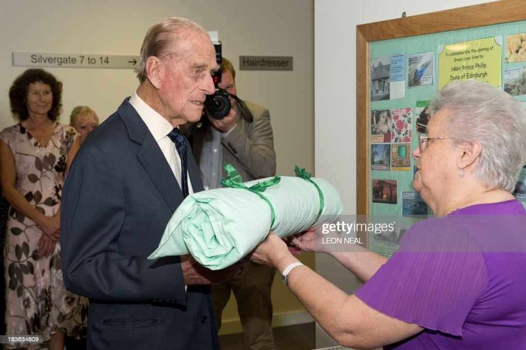 Britain's Prince Philip (L) is presented with a quilt containing advice for Prince George from the residents of the Green Lane View care complex during an official visit to the St Michael's Care Complex in Aylsham, eastern England, on October 8, 2013.