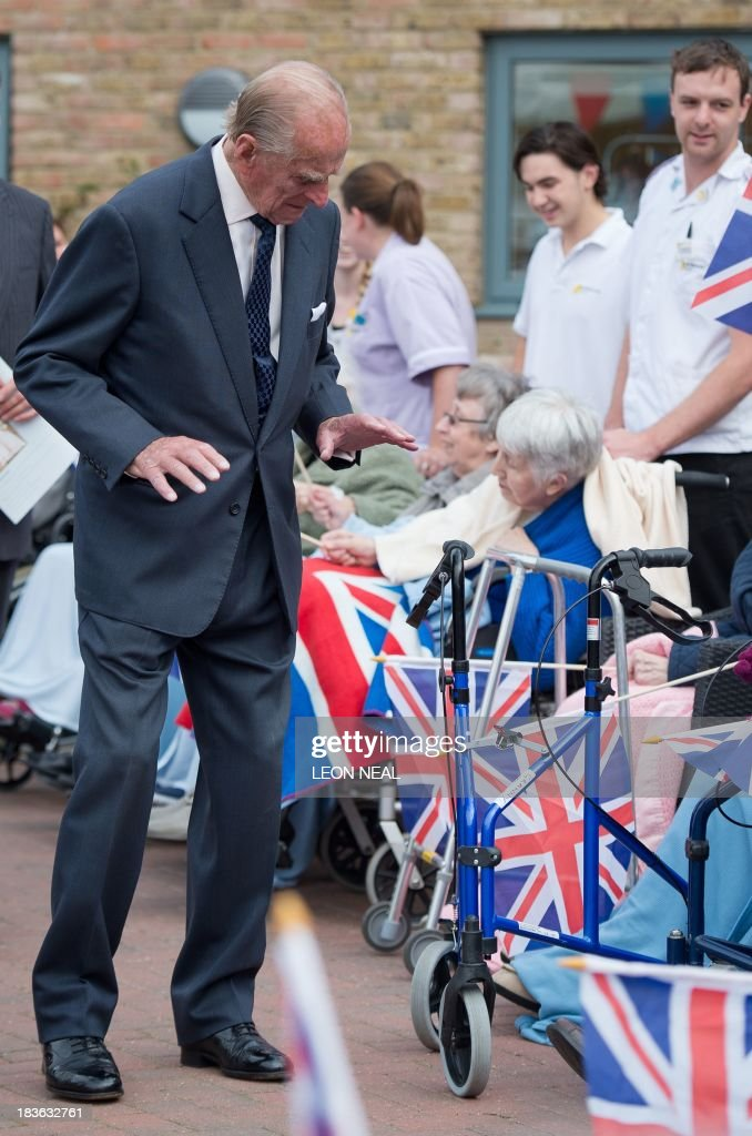 Britain's Prince Philip reacts after seeing a rollator walking frame while meeting residents of the St Michael's Care Complex in Aylsham, eastern England, during an official visit on October 8, 2013.