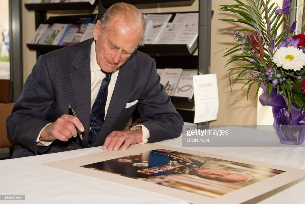 Britain's Prince Philip signs a portrait during an official visit to the St Michael's Care Complex in Aylsham, eastern England, during an official visit on October 8, 2013.