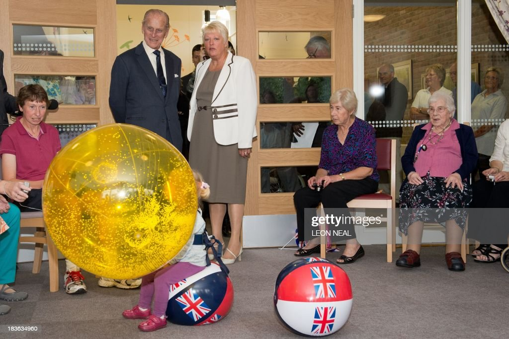 Britain's Prince Philip (2nd L) watches residents as they exercise in the Green Lane View assisted-living residential home during an official visit to the St Michael's Care Complex in Aylsham, eastern England, on October 8, 2013.