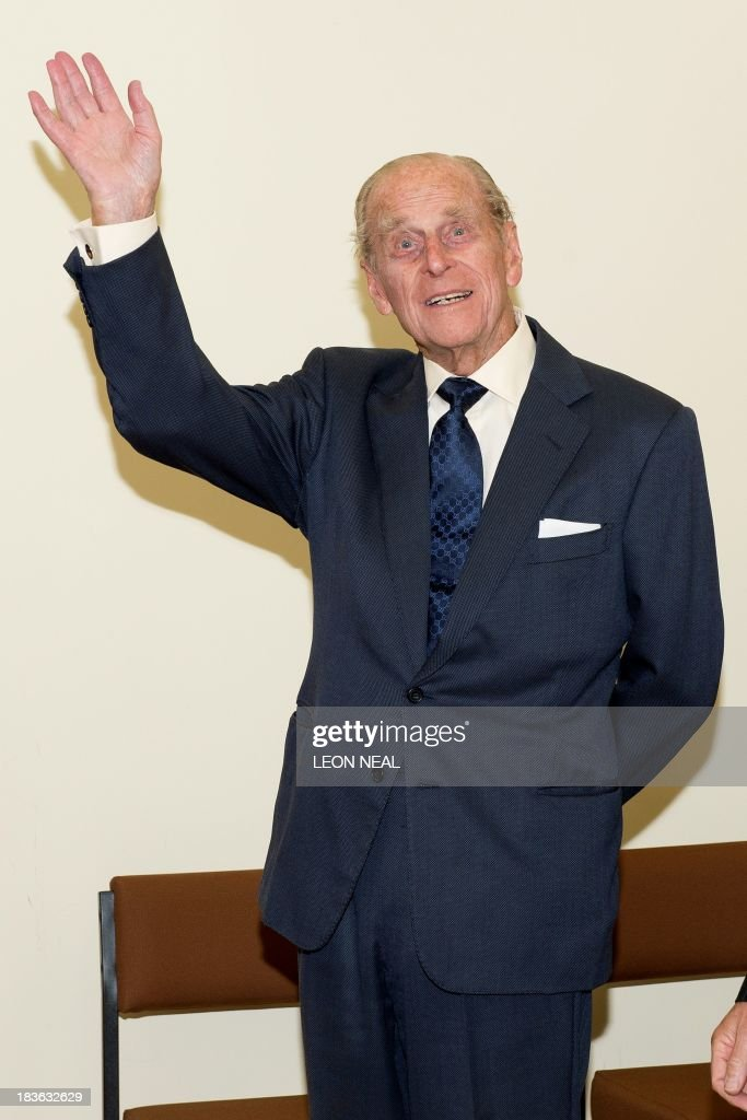 Britain's Prince Philip waves after seeing pupils of the Broadland School of Dance perform in the ACT centre of the St Michael's Care Complex in Aylsham, eastern England, during an official visit on October 8, 2013.