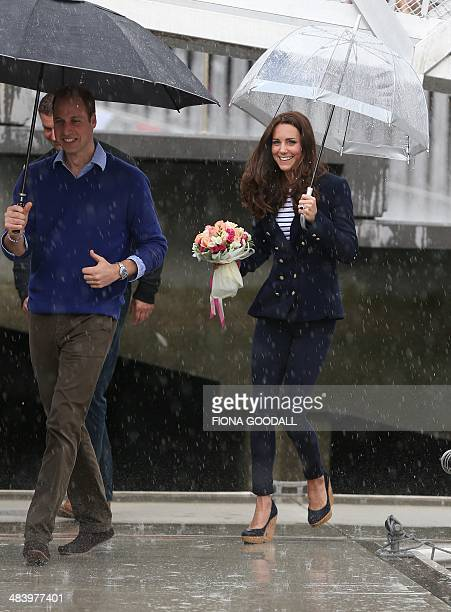 Britain's Prince William and his wife Catherine battle the elements as they arrive to sail on Team New Zealand's America's Cup yachts on Auckland...