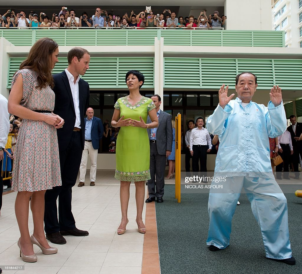 Britain's Prince William (2nd L) and his wife Catherine (L), the Duchess of Cambridge, watch a man (R) practicing 'tai chi' during their visit to Strathmore Green, a precinct in Queenstown, a residential district of Singapore on September 12, 2012. Britain's Prince William and his wife Catherine arrived in Singapore on September 11 to kick off a nine-day Southeast Asian and Pacific tour marking Queen Elizabeth II's Diamond Jubilee. AFP PHOTO / POOL / Nicolas ASFOURI