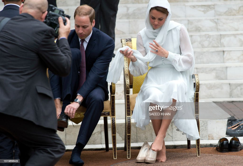 Britain's Prince William and his wife Catherine, the Duchess of Cambridge wear their shoes after visiting the KLCC Mosque in Kuala Lumpur on September 14, 2012, on the second leg of a nine-day Southeast Asian and Pacific tour marking Queen Elizabeth II's Diamond Jubilee. AFP PHOTO / Saeed Khan